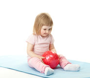 Baby girl with a ball. Happy baby girl doing exercises with a ball sitting on a mat; white background Stock Image