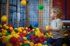 Baby girl in ball pool. Little child in a ball pool Royalty Free Stock Image