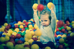 Baby girl in ball pool. Little child in a ball pool Stock Photo