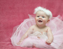 Baby girl ballerina. Cute baby girl  sitting on pink background in ballet dress smilling Royalty Free Stock Image