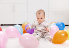 Baby girl with balloons Stock Image