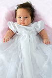 Baby Girl In Baptism Dress. Newborn baby girl in a white baptism dress on a pink blanket stock photos