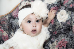 Baby Girl In Baptism Dress. Newborn baby girl in a white baptism dress on a flower cushion stock image