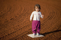 Baby girl on baseball diamond stock photo