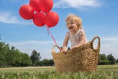 Baby Girl in a Basket with Red Balloons. Baby girl one year old in a basket with red balloons, green grass and blue cloudy sky on background, outdoor. Girl is Royalty Free Stock Photos