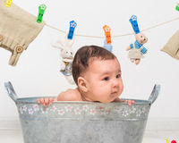 Baby girl bathes in a  trough Stock Photos