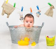 Baby girl bathes in a  trough Stock Image