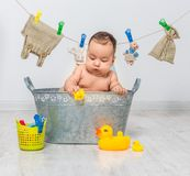Baby girl bathes in a  trough Royalty Free Stock Photo