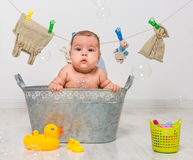 Baby girl bathes in a  trough Royalty Free Stock Images