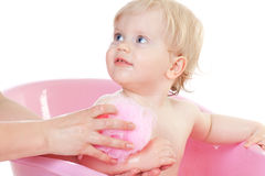 Baby girl bathing in the bath Stock Photos