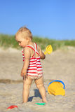 Baby girl on a beach. With plastic toys Royalty Free Stock Photo