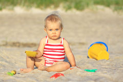 Baby girl on a beach. With plastic toys Stock Photography