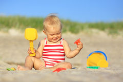 Baby girl on a beach. With plastic toys Stock Images