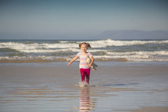 Baby girl on the beach. Baby girl running through the sea on the beach with a teddy under her arms Royalty Free Stock Photos