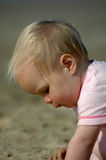Baby girl on beach. Closeup of a baby girl in profile playing in the sand on a beach Royalty Free Stock Images
