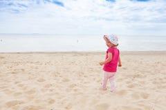 Baby girl beach. Little baby girl standing at the beach stock photos