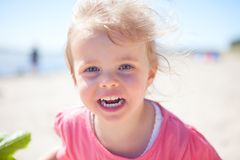 Baby girl beach. Little girl l at the beach having fun, close up, smiling royalty free stock photography