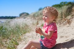 Baby girl beach. Little girl l at the beach having fun looking to the sea and smiling stock photos