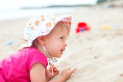 Baby girl beach. Little baby girl at the beach playing with sand toys stock photos