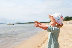 Baby girl beach. Little baby girl standing at the beach and pointing into the distance royalty free stock photos