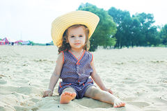 Baby girl on a beach in a straw hat Stock Photos