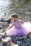 Baby girl. Beautiful brunette baby girl sitting on pebble beach Stock Photography