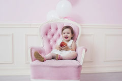 Baby girl beautiful and happy pink interior with vintage chair a Stock Image
