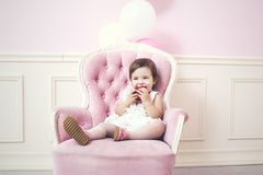 Baby girl beautiful and happy pink interior with vintage chair a Stock Images