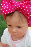 Baby girl. Beautiful girl with a pink bow on her head stock photo