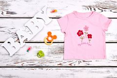 Baby-girl beautiul pink t-shirt. Infant girl cotton cartoon pink t-shirt, pacifier, teether, hair accessory on white wooden background Royalty Free Stock Photo