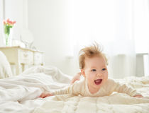 Baby girl on the bed. Beautiful smiling cute baby girl on the bed in the room. Happy child laughing Stock Photos