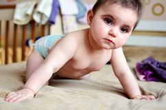Baby girl on a bed. Cute baby girl crawling on bed royalty free stock photos