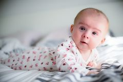 Baby girl on a bed looking at camera royalty free stock images