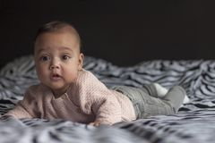Baby girl on bed looking surprised stock photography