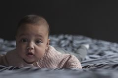 Baby girl on bed lying on belly holding head up royalty free stock photography