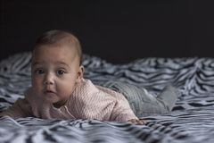 Baby girl on bed with a sad face stock photography