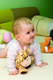 Baby girl in bed with toys  Royalty Free Stock Images