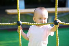 Baby girl behind a rope net Stock Image