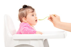 Baby girl being fed in a feeding chair Stock Photo