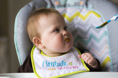 Baby girl being fed. Happy baby girl full of expressions during her feeding from mom stock photography