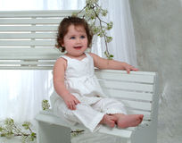 Baby Girl on bench stock photo