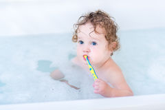 Baby girl with big blue eyes brushing her teeth Stock Image