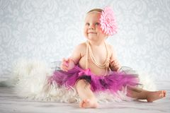 Baby girl with big flower on head. Cute baby girl with pearls and tutu skirt - studio shot Stock Photography