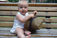 A baby girl with a big hat sitting on the bench Royalty Free Stock Image