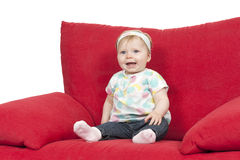 Baby girl in a big red sofa Stock Image