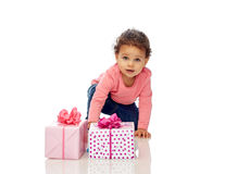 Baby girl with birthday presents and confetti Stock Photography