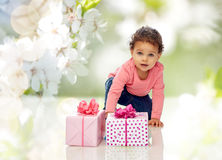 Baby girl with birthday presents and confetti Stock Photos