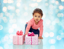 Baby girl with birthday presents and confetti Royalty Free Stock Images