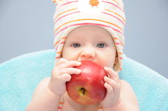 Baby girl bite organic apple Stock Photo