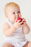 Baby girl biting an apple. Portrait of a little girl with red apple royalty free stock images
